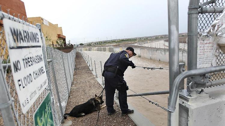 Henderson Police Officer James Mitchell and his dog Xaro conduct a search of the Duck Creek Channel for 17-year-old Green Valley High School student William Mootz in Henderson, Nev.  on Aug. 22, 2012.  Crews resumed the search Thursday for Mootz, who somehow fell into a drainage wash in Henderson,  which had filled quickly after a morning downpour a day earlier.  (AP Photo/Las Vegas Review-Journal, Jason Bean)