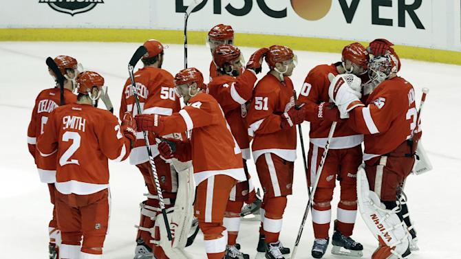 Detroit Red Wings players celebrate their 2-0 win over the Chicago Blackhawks after Game 4 of the Western Conference semifinals in the NHL hockey Stanley Cup playoffs in Detroit, Thursday, May 23, 2013. (AP Photo/Paul Sancya)