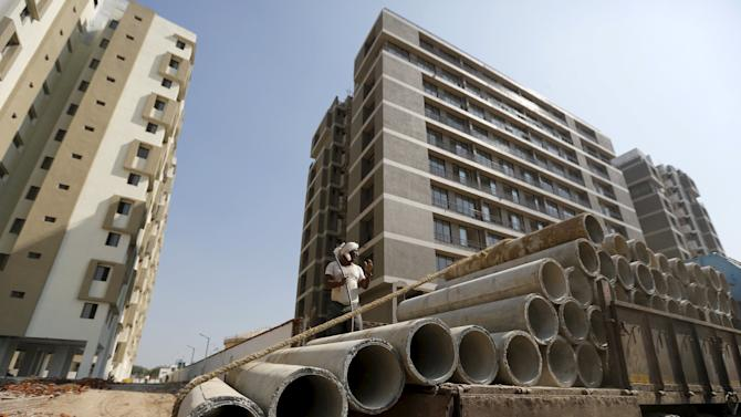 A labourer unloads sewage pipes from a truck at the construction site of residential buildings on the outskirts of Ahmedabad
