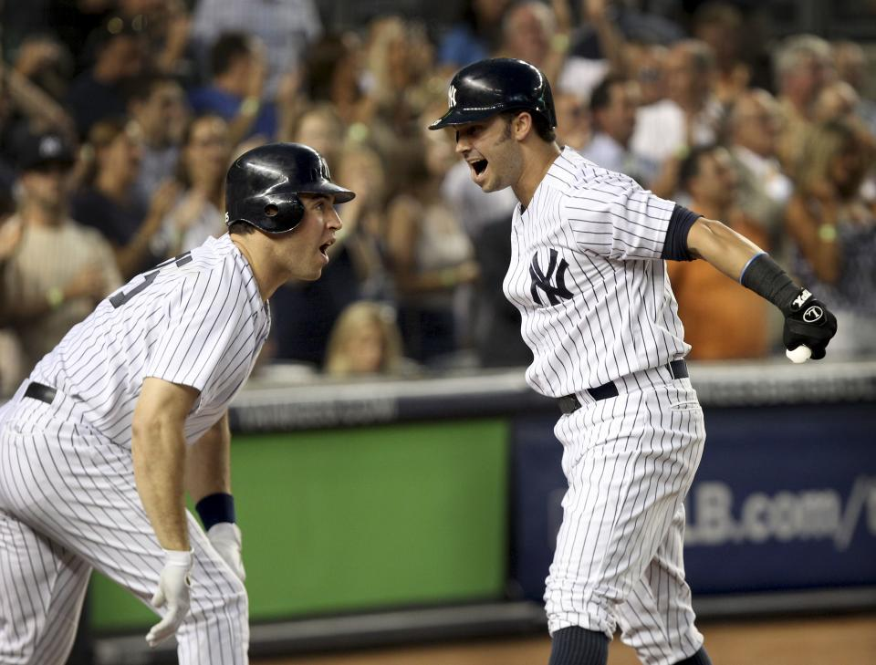 New York Yankees' Nick Swisher, right, celebrates his grand slam with Mark Teixeira during the third inning of the baseball game against the Texas Rangers Monday, Aug. 13, 2012 at Yankee Stadium in New York.  (AP Photo/Seth Wenig)