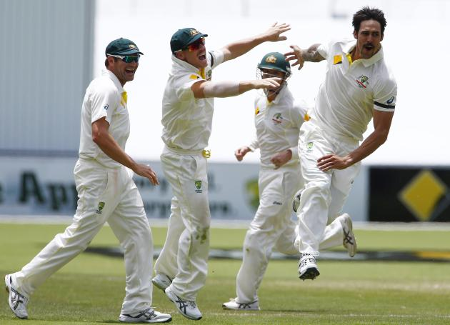 Australia's Johnson celebrates with team mates after taking the wicket of England's Broad during the third day's play in the second Ashes cricket test at the Adelaide Oval