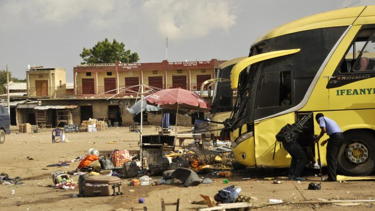 Bomb experts study the damage to a bus at the scene of a bomb explosion, at the Sabon Gari bus park in Kano