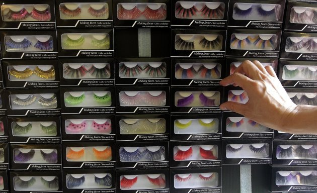 Woman picks up a box of fake eyelashes at a stall in the Ximending shopping district of Taipei