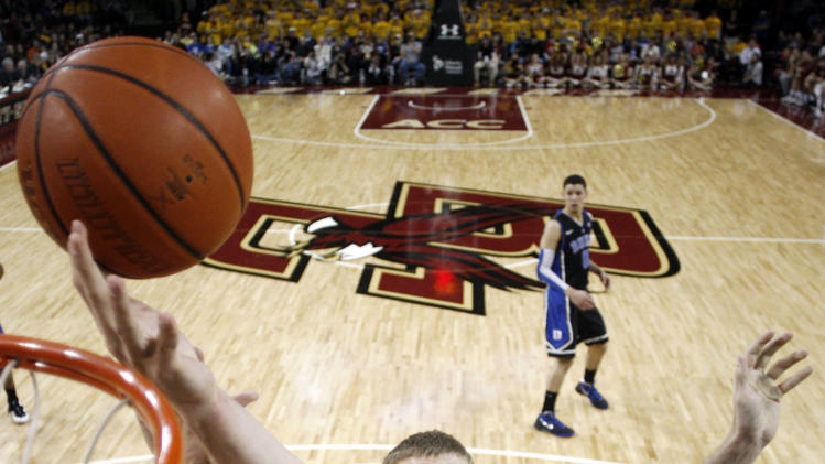 Duke's Mason Plumlee (5) grabs a rebound over Boston College's Ryan Anderson during the second half of Duke's 75-50 win in an NCAA college basketball game in Boston, Sunday, Feb. 19, 2012. (AP Photo/Winslow Townson)