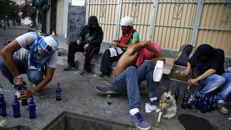 Anti-government protesters prepare Molotov cocktails during riots with police in Caracas