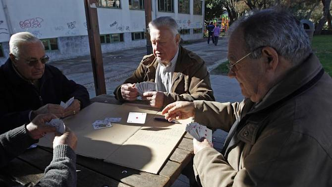 Pensioners play cards at a garden in Alges on the outskirts of Lisbon