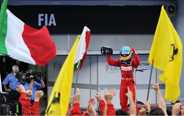 Ferrari driver Fernando Alonso of Spain celebrates after winning Formula One's Malaysian Grand Prix at the Sepang International Circuit in Sepang on March 25, 2012.  AFP PHOTO / ROSLAN RAHMAN (Photo c