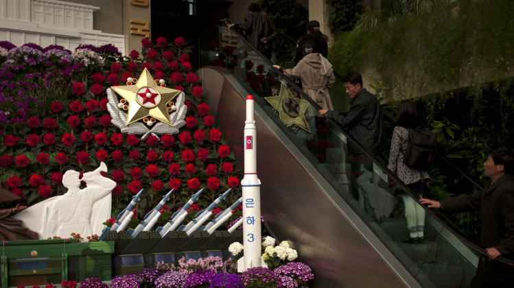 People visit a flower show featuring thousands of Kimilsungia flowers, named after the late leader Kim Il Sung, while models of a rocket and missiles are also displayed in Pyongyang, North Korea, Friday, April 12, 2013. (AP Photo/Alexander F. Yuan)