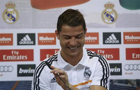 Real Madrid's Cristiano Ronaldo reacts as he attends a news conference to discuss the draw for the 2014 World Cup at the Valdebebas training grounds, outside Madrid, December 8, 2013. REUTERS/Javi