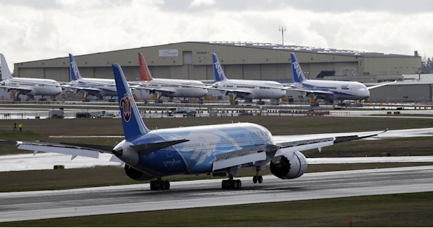 This photo taken Feb. 7, 2013 show a Boeing 787 jet landing, in view of a line of parked 787's at Paine Field in Everett, Wash. Boeing has developed a plan that it intends to propose to federal regula