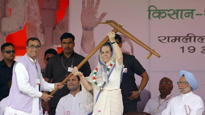 India's Congress party president Sonia Gandhi lifts a plough given to her by the head of the party's Delhi branch Ajay Maken during a farmers' rally at Ramlila ground in New Delhi