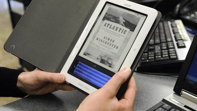 FILE - In this Feb. 4, 2011 file photo, Heather Stephenson, a librarian at the Siouxland Library main branch, demonstrates how to download a book from siouxlandlib.org onto an e-reader. E-book readers have been relatively slow to borrow digital works from the library, frustrated by a limited selection and by not even knowing if their local branch offers e-releases, according to a survey published Friday, June 22, 2012 by the Pew Research Center. (AP Photo/The Argus Leader, Emily Spartz, File)