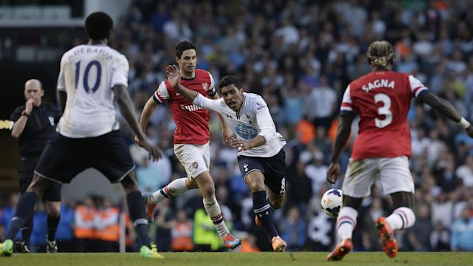 Tottenham Hotspur's Paulinho, falls after being fouled by Arsenal's Mikel Arteta during the English Premier League soccer match between Tottenham Hotspur and Arsenal at White Hart Lane stadium in London, Sunday, March 16, 2014