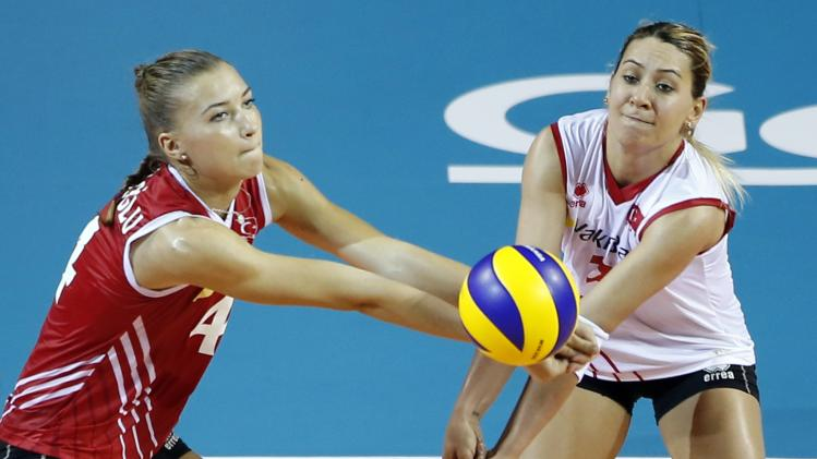 Meliha Ismailoglu and Gizem Karadayi of Turkey attempt to receive the ball during their FIVB Women's Volleyball World Grand Prix 2014 final round match against Brazil in Tokyo
