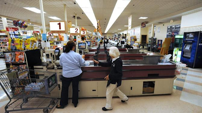 In this Sept. 23, 2011 photo, cashier Joyce Mackie, right, comes to the aid of a customer having a problem at a self-serve checkout station at a Big Y supermarket in Manchester, Conn. A growing  number of supermarket chains are bagging their self-serve checkout lanes, saying they can offer better customer service when clerks help shoppers directly. Big Y Foods, which has more than 60 southern New England locations, recently became the latest to announce it's phasing them out.  (AP Photo/Jessica Hill)