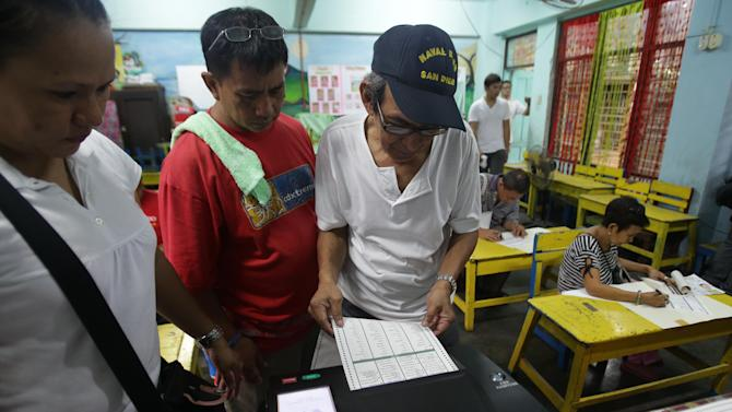 A Filipino man enters the first vote of his precinct at a school used as a voting center during mid-term elections at a school in Manila, Philippines on Monday, May 13, 2013. The country is electing local officials from senators to congressmen and down to municipal mayors during Monday's mid-term elections. (AP Photo/Aaron Favila)