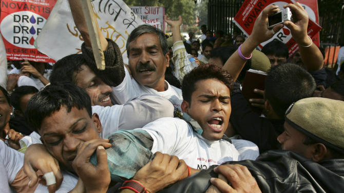 FILE – In this Jan. 29, 2007 file photo, Indian police officers block demonstrators protesting against Swiss drugmaker Novartis AG's case against the Indian government on drug patents in New Delhi, India. India's Supreme Court is to rule Monday, April 1, 2013, whether to deny a patent to Novartis AG for its cancer treatment in a landmark case that would allow Indian companies to continue producing cheaper versions of many lifesaving medicines.  (AP Photo/Saurabh Das, File)