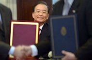 China's Prime Minister Wen Jiabao is seen while Chinese and Argentine ministers exchange documents at the end of the signing agreemets ceremony at the Government Palace in Buenos Aires