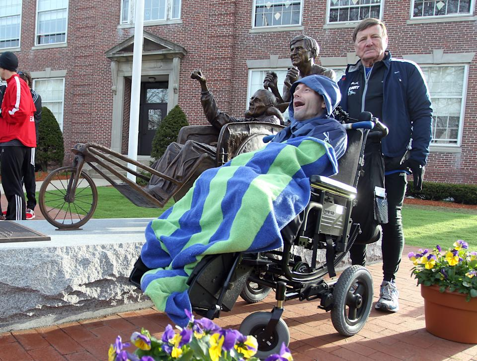 Dick Hoyt, right, and his son, Rick, stand next to a statue honoring them near the start of the 117th running of the Boston Marathon, in Hopkinton, Mass., Monday, April 15, 2013. (AP Photo/Stew Milne)