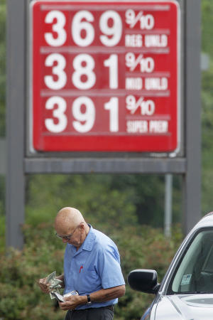 George Matkowski, of Montpelier, reaches into his wallet to pay for gas, Friday, Aug. 10, 2012, in Montpelier, Vt. A rise in the price of crude oil and problems with refineries and pipelines in the West Coast and Midwest have caused prices at the pump to surge upward. (AP Photo/Toby Talbot)