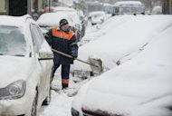 A municipal worker clears between snow-covered cars in Moscow last week. Thousands of drivers waited for hours without moving in their lorry cabs Sunday in temperatures of minus five degrees Celsius (23 degrees Fahrenheit).