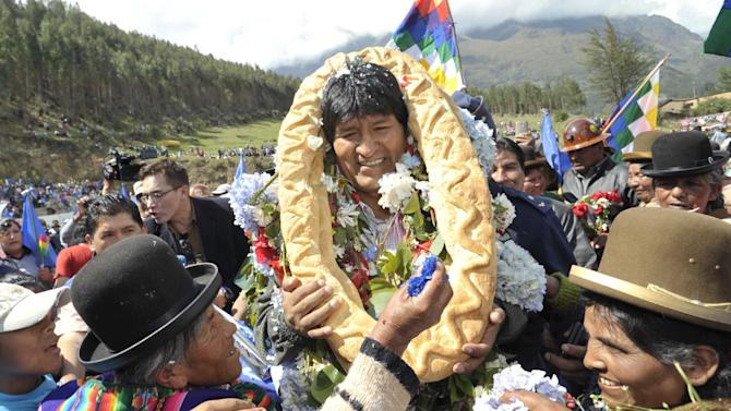 Bolivia's President Evo Morales is greeted by residents with a garland made of bread in Quime, southeast of La Paz