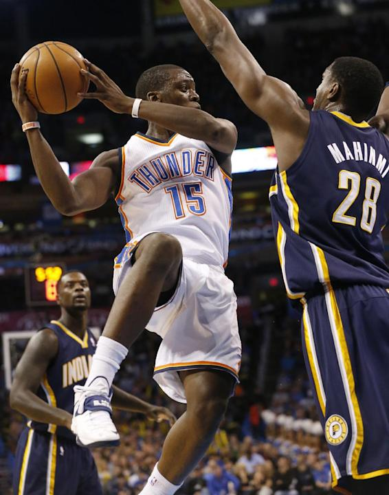 Oklahoma City Thunder guard Reggie Jackson (15) passes around Indiana Pacers center Ian Mahinmi (28) in the second quarter of an NBA basketball game in Oklahoma City, Sunday, Dec. 8, 2013