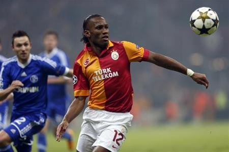 Galatasaray's Drogba is challenged by Schalke 04's Hoger during their Champions League soccer match in Istanbul