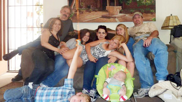 FILE - In this June 2011 file photo provided by Andrea Saincome, Hannah Anderson, center, reclining across the laps of others, and James Lee DiMaggio, right, pose for a picture with other members of the extended Anderson and Saincome families. Via a social media site, Hannah Anderson says longtime family friend DiMaggio