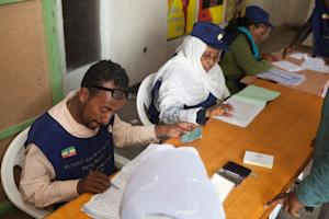 Ethiopian Electoral Board employees check voters names…