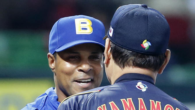 Managers Barry Larkin, left, of Brazil and Koji Yamamoto of Japan shake hands during the opening ceremony before the World Baseball Classic first round game between Japan and Brazil at Yahoo Dome in Fukuoka, Japan, Saturday, March 2, 2013. (AP Photo/Koji Sasahara)