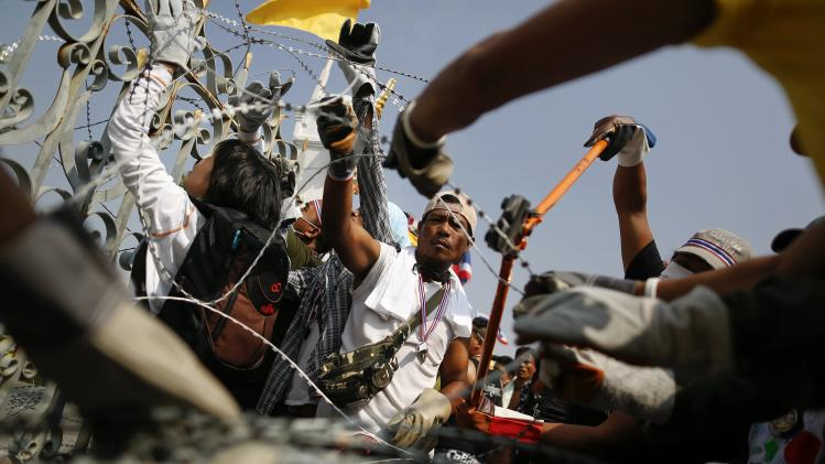 Anti-government protesters remove barbed wire before a small group of them briefly entered the compound of the Government House in Bangkok