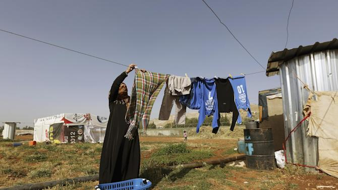 """FILE - In this Thursday, June 19, 2014 file photo, a Syrian refugee woman hangs laundry at a Syrian refugee camp in the eastern Lebanese town of Majdal Anjar, Lebanon. The Lebanese government said Thursday, Oct. 23, that the tiny Mediterranean country will not accept any more Syrian refugees except for what authorities deem to be """"exceptional"""" cases. Jreij said the government will ask the U.N. refugee agency, known as UNHCR, not to register any more cases in Lebanon and that Syrian refugees already here would be """"encouraged to return to their country"""" or go elsewhere. (AP Photo/Bilal Hussein, File)"""