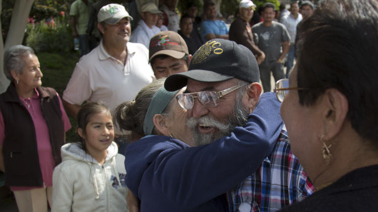 A woman embraces self-defense group spokesman Estanislao Beltran in Tancitaro, Michoacan, Mexico, Thursday, Jan. 16, 2014. Mexico's spreading vigilante movement announced its first big land hand-out, returning 25 avocado orchards to farmers whose properties had been seized by the cartel, which started in drug trafficking and expanded to extortion and economic control. Such moves are expanding the strength and popularity of the vigilantes even as the government demands they disarm. (AP Photo/Eduardo Verdugo)
