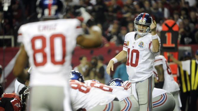 New York Giants quarterback Eli Manning (10) speaks to Giants wide receiver Victor Cruz (80) against the Atlanta Falcons during the first half of an NFL football game on Sunday, Dec. 16, 2012, in Atlanta. (AP Photo/John Amis)