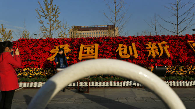 """In this photo taken Monday, Nov. 12, 2012, a woman poses for photos near floral decorations with the Chinese characters for """"Patriotism, Innovation"""" set up for the 18th Communist Party Congress held in Beijing, China. The Chinese capital's administrators havebedecked the city with towers of flower installations and othereye-catching landscaping decorations. State media say 20 million pots of flowers are being used in more than ahundredlocationsin preparation for the once-a-decade party congress to usher in a new generation ofleaders.  (AP Photo/Vincent Yu)"""