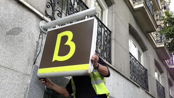 A worker puts in place a Bankia logo at a Bankia branch in Madrid