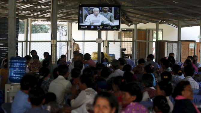 People watch as Khieu Samphan is seen in a television screen at the Extraordinary Chambers in the Courts of Cambodia, on outskirts of Phnom Penh