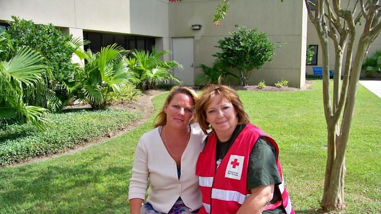 In this Sept. 11, 2012 photo provided by the American Red Cross, Brenda LaFlamme, left, waits outside Ochsner Medical Center-North Shore in Slidell, La., with Deborah Kemp, of Ann Arbor, Mich., a volunteer with the American Red Cross Safe and Well program. Kemp reunited LaFlamme with her father, Larry Bailey, who was treated at the hospital after being rescued from Hurricane Isaac's floods on Aug. 30, 2012. He had been brought to the emergency room several days after the rescue, incoherent and bleeding from an infected month-old wound.  (AP Photo/American Red Cross, Louis Palm)