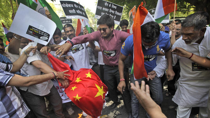 Indian protestors burn a Chinese flag and shout slogans against the alleged incursion by Chinese troops into Indian territory, during a protest in New Delhi, India, Wednesday, May 1, 2013. India said Chinese troops crossed the de facto border between the countries and went 10 kilometers (six miles) into Indian territory on April 15. About 50 Chinese soldiers have pitched tents and are camping in Daulat Beg Oldi in the Ladakh region of eastern Kashmir.   (AP Photo /Manish Swarup)