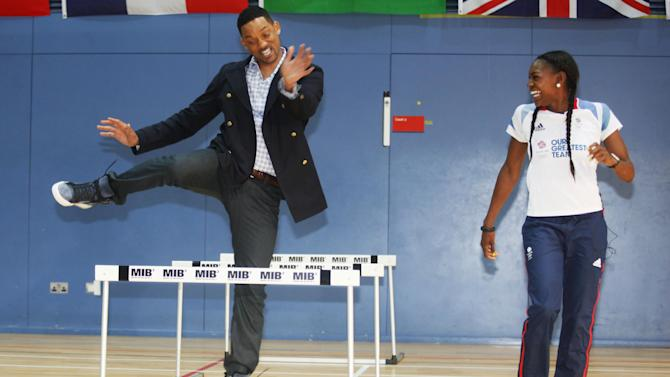 Actor Will Smith tries the hurdles with Great Britain Olympic 400m hurdler Perri Shakes-Drayton at Ethos gym in London, Wednesday, May 16, 2012. (AP Photo/Jim Ross)