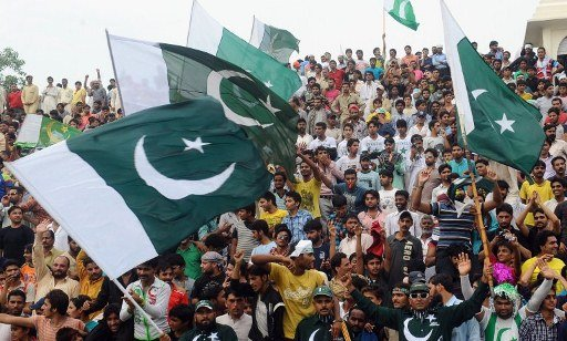 Pakistanis waves their national flags during a ceremony to celebrate Pakistan's Independence Day on the Pakistan-India border at Wagah on August 14, 2012.  Pakistan on August 14 celebrated its 65th an