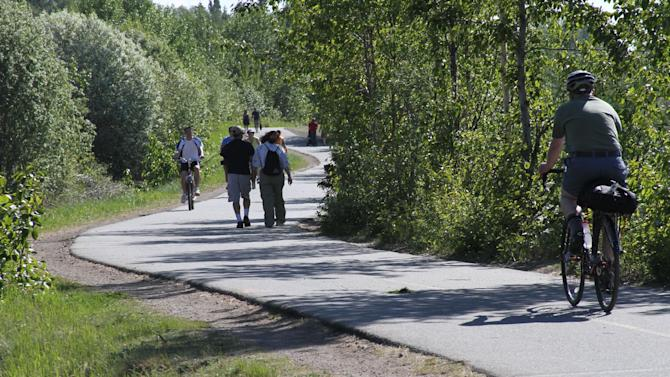 This photo taken June 11, 2013, shows people using the Tony Knowles Coastal Trail in downtown, Anchorage, Alaska. Anchorage offers more than 135 miles of multi-use trails in the city. (AP Photo/Mark Thiessen)