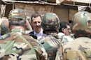 Syria's President Assad chats with military personnel during his visit to a military site in the town of Daraya