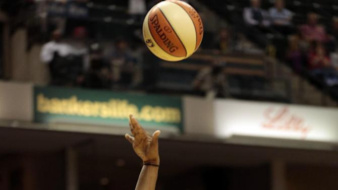 Indiana Fever forward Tamika Catchings, right, shoots in front of Atlanta Dream's Angel McCoughtry during the second half of a WNBA basketball first-round playoff game in Indianapolis, Tuesday, Oct. 2, 2012. The Fever won 75-64. (AP Photo/AJ Mast)
