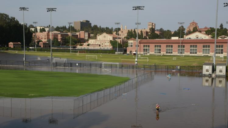 A person walks through the flooded Drake Field on the UCLA campus, caused by a broken thirty inch water main in the Westwood section of Los Angeles