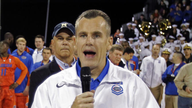 Florida head coach Billy Donovan announces to fans that the second half of the Navy-Marine Corps Classic NCAA college basketball game against Georgetown had been canceled due to heavy condensation on the court aboard the USS Bataan at the Mayport Naval Station, Friday, Nov. 9, 2012, in Jacksonville, Fla. (AP Photo/John Raoux)
