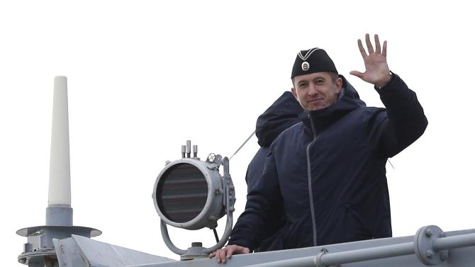 A Russian sailor waves from the deck of the Russian Navy frigate Smolny as the ship leaves the STX Les Chantiers de l'Atlantique shipyard site in Saint-Nazaire