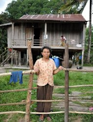 Cambodian Yi Chhav, a 68-year-old widow, stands in front of her home in Koh Kong province. Rights groups say the government has ignored residents' legitimate land claims by granting tens of thousands of hectares to local and foreign-owned sugar firms across the nation