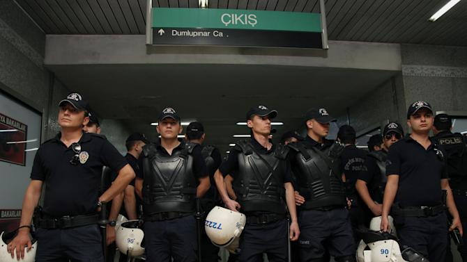 "Riot police stand at the entrance as young Turkish couples expected to kiss in protest against subway official's harassment of a couple for kissing in public last week, at a subway stop in Ankara, Turkey, Saturday, May 25, 2013.  Last week, Ankara subway officials made a reproaching announcement asking passengers ""to act in accordance with moral rules,"" after spotting the couple kissing through security cameras. (AP Photo/Burhan Ozbilici)"